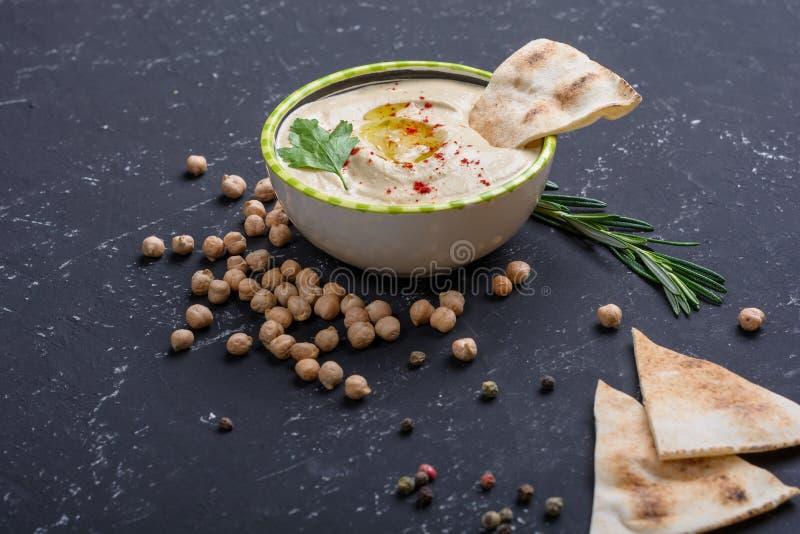 Hummus caseiro, feijões do grão-de-bico, alecrins com o pão árabe na tabela de pedra preta Culinária árabe tradicional e autêntic foto de stock royalty free