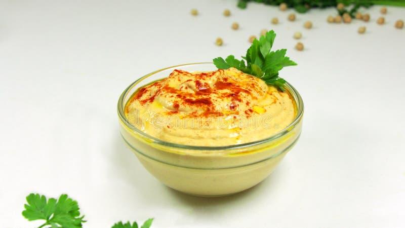 Hummus clássico em uma bacia de vidro em uma tabela branca imagem de stock royalty free