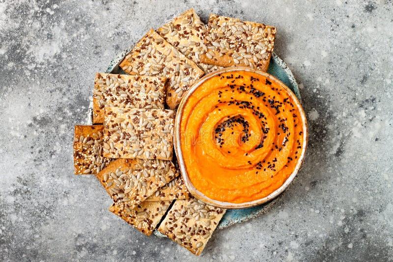 Hummus della zucca esperto con olio d'oliva e semi di sesamo neri con gli interi cracker del grano Aperitivo o spuntino vegetaria fotografia stock libera da diritti