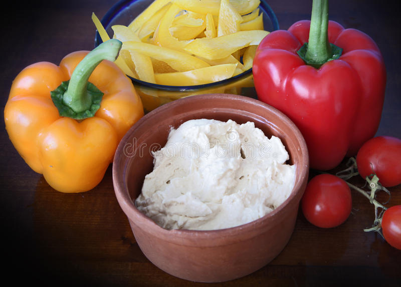 Hummus dip, peppers and tomatoes. Hummus with red and yellow peppers and pepper slices ready to dip stock images