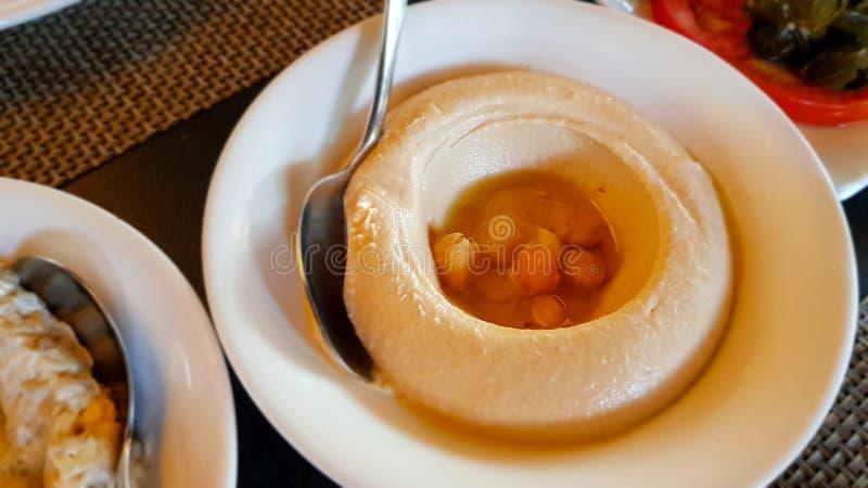 Hummus, dopp eller spridning som göras av blandad kikärtar, sesamtahini, citronjuice och vitlök och ätas typisk med pitabröd fotografering för bildbyråer