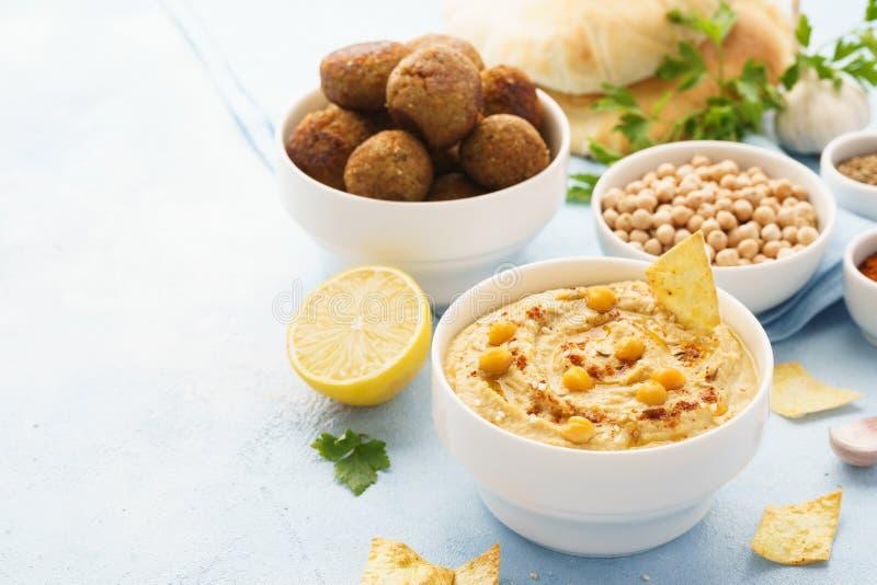 Hummus dopp med chiper, pitabrödet och falafelen sund mat arkivfoto