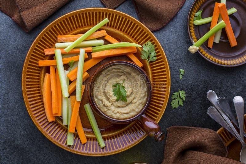Hummus dopp med grönsaker royaltyfri fotografi