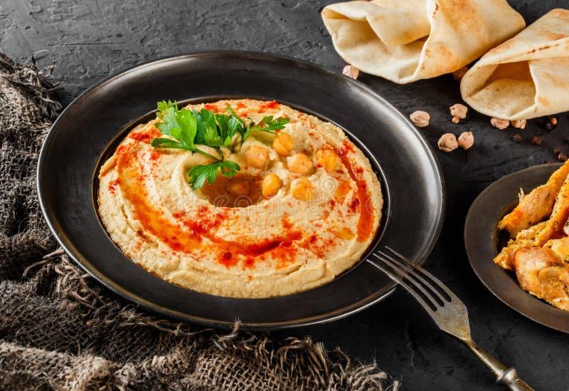 Hummus dos grãos-de-bico com azeite, paprika em uma placa sobre o fundo de pedra escuro O alimento saudável do vegetariano, limpa foto de stock royalty free