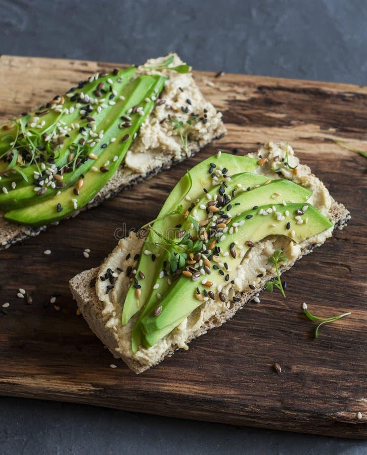 Hummus e sanduíche do baguette do abacate com as sementes do sésamo e de linho em uma placa de corte de madeira, em um fundo cinz fotografia de stock royalty free