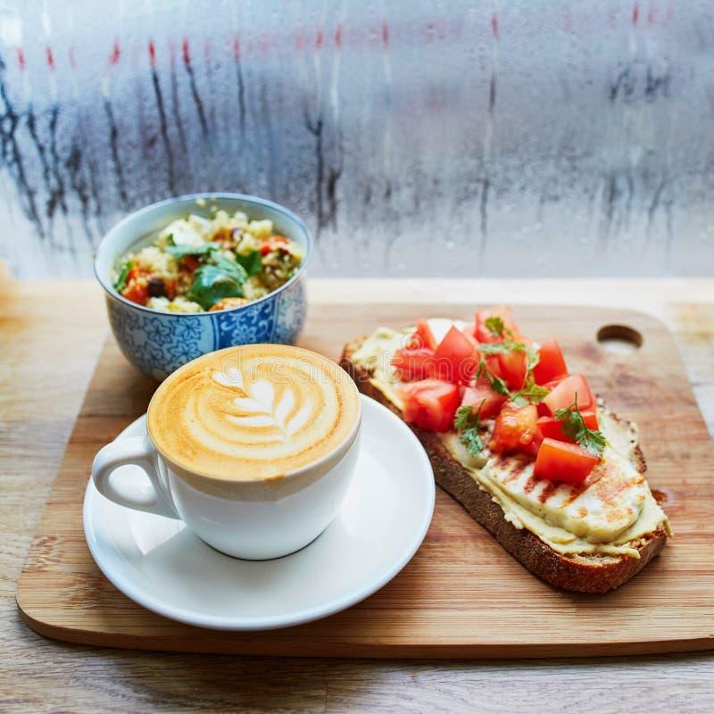 Hummus en tomatensandwich, salade en verse hete cappuccinokoffie royalty-vrije stock fotografie