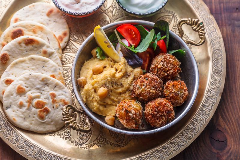 Hummus, falafel, салат и пита в медном лотке стоковые изображения