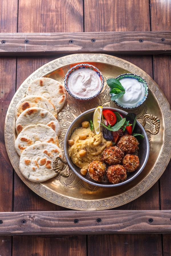 Hummus, falafel, salada e pão árabe em uma bandeja de cobre foto de stock