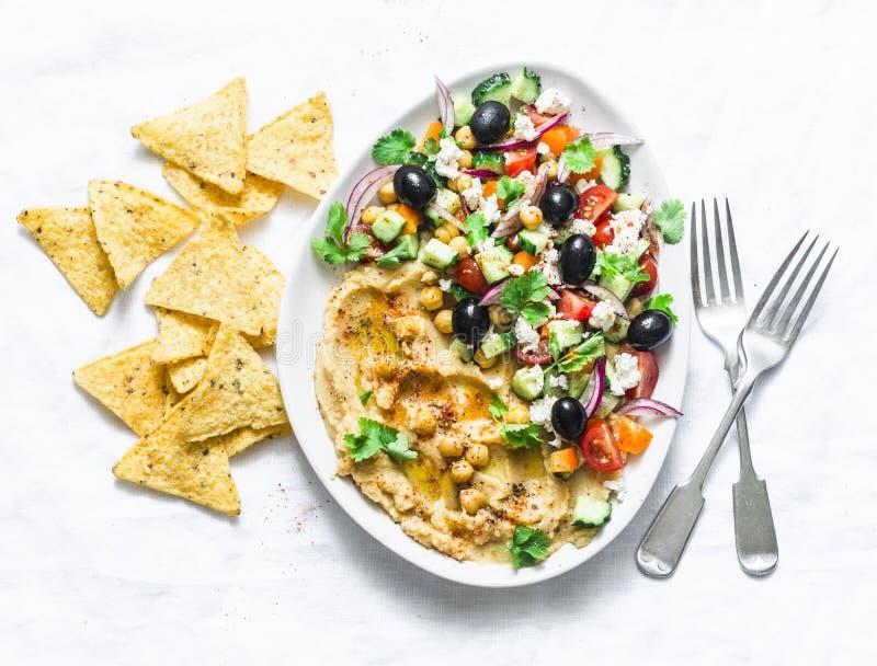 Hummus greco caricato dell'insalata con i chip di tortiglia del cereale su fondo leggero, vista superiore Aperitivo delizioso, ta immagini stock