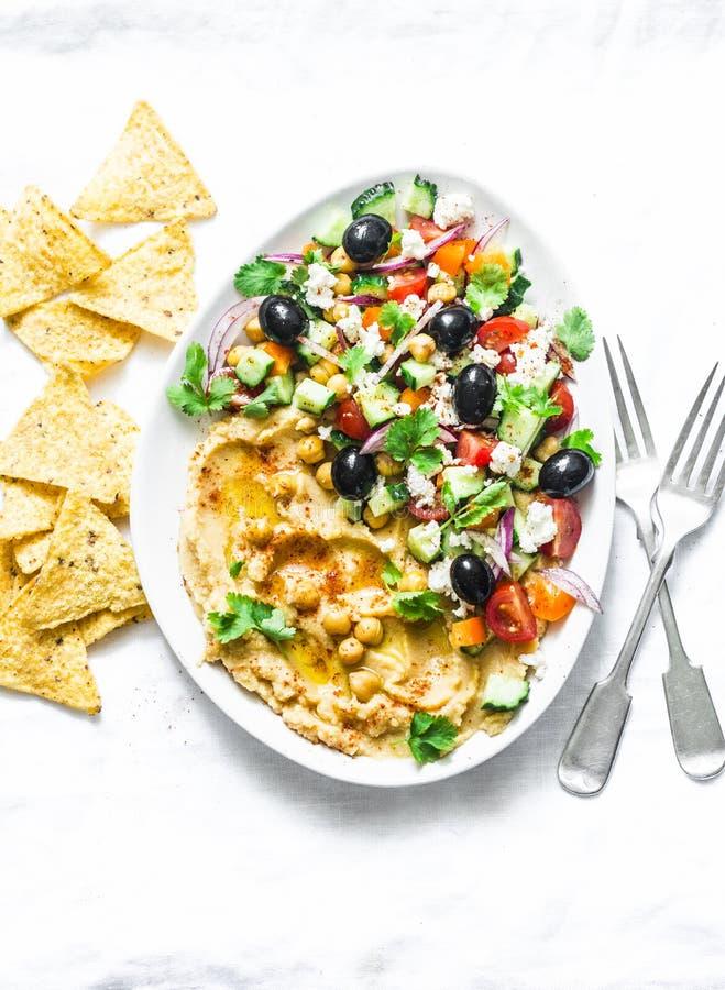 Hummus greco caricato dell'insalata con i chip di tortiglia del cereale su fondo leggero, vista superiore Aperitivo delizioso, ta immagini stock libere da diritti