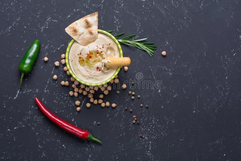 Hummus hecho en casa con las barras de pan de la pita y del grissini en la tabla de piedra negra Cocina árabe tradicional y autén imagen de archivo