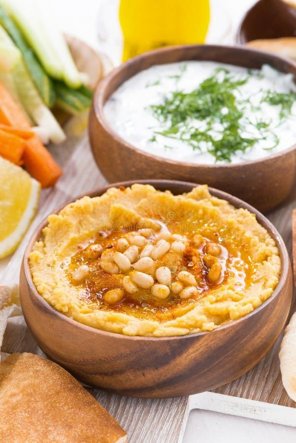 Hummus i träbunke med pitabröd och nya grönsaker royaltyfri bild