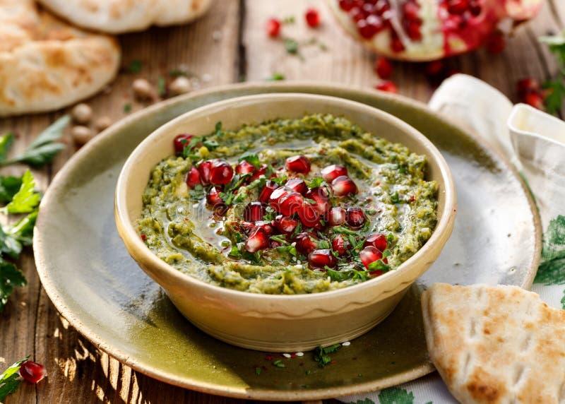 hummus Kruidhummus met de toevoeging van granaatappelzaden, peterselie, olijfolie en aromatische kruiden in een ceramische pot op stock afbeelding