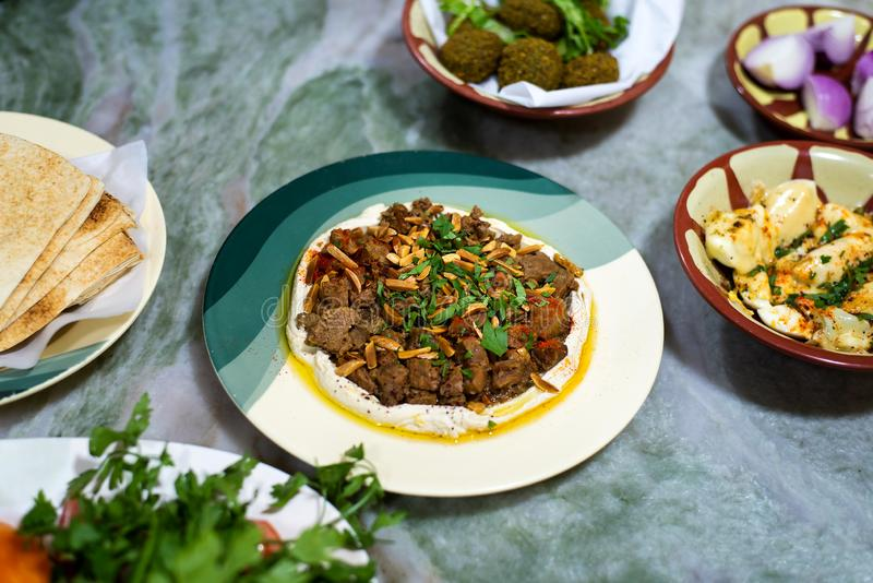 Hummus and meat with arabic snacks on a table stock image