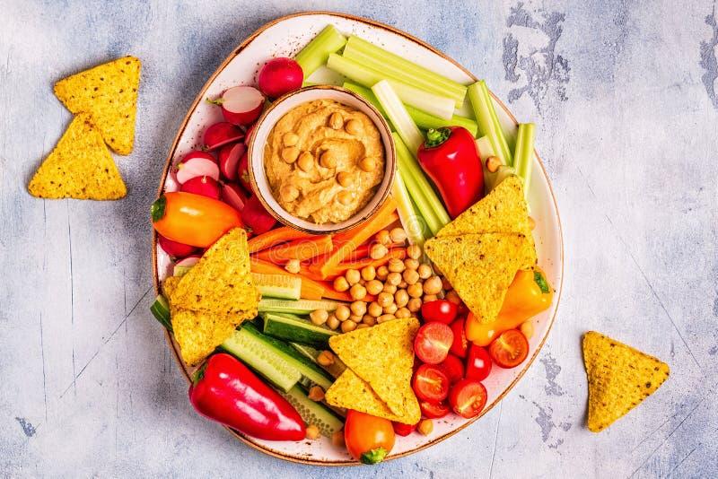 Hummus med olika nya rå grönsaker royaltyfria foton