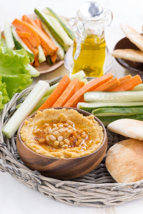 Hummus med pitabröd och nya grönsaker, lodlinje royaltyfri foto