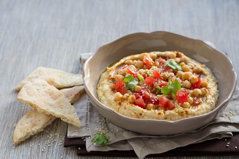 Hummus met een salade van tomaat, ui en koriander royalty-vrije stock afbeelding