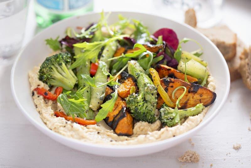 Hummus met geroosterde groenten en salade stock fotografie