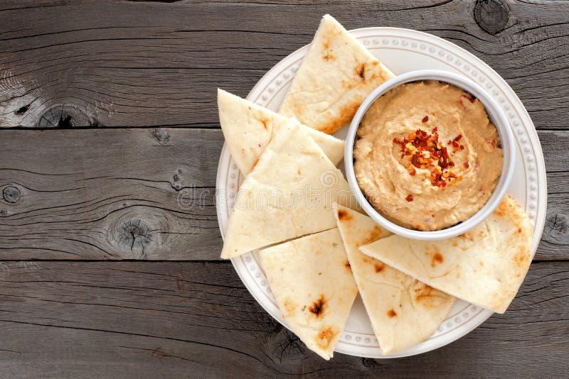 Hummus met pitabroodje op een plaat, boven mening over hout royalty-vrije stock foto