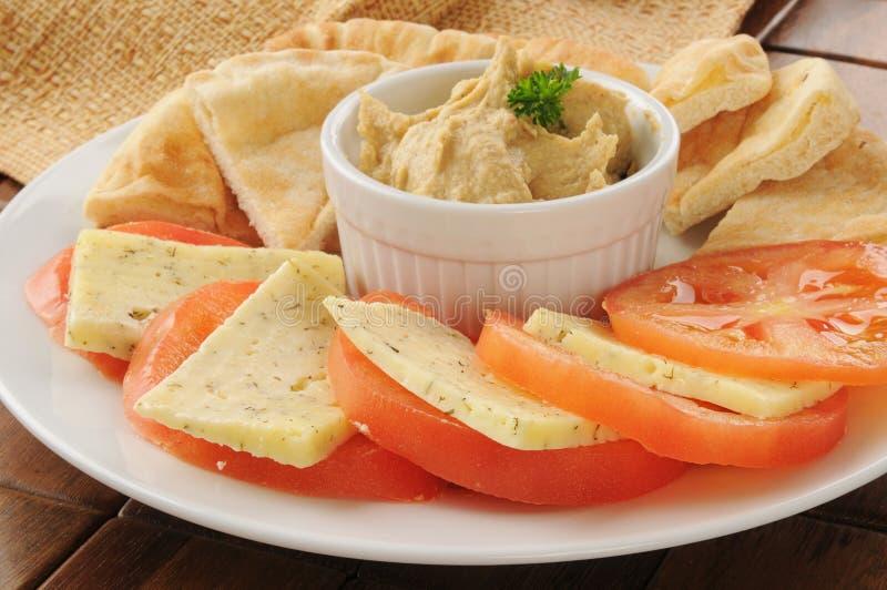 Hummus met tomaat, kaas en pitabroodje stock fotografie