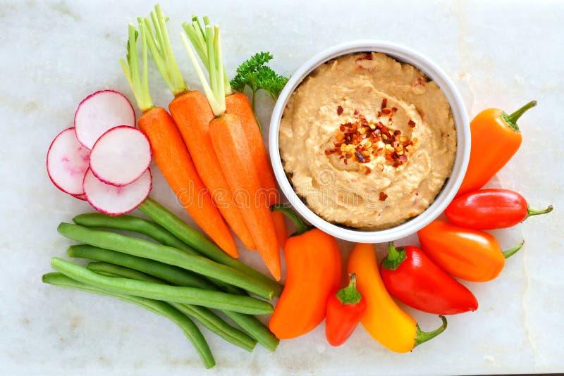 Hummus met verse groenten, boven mening over wit marmer stock foto
