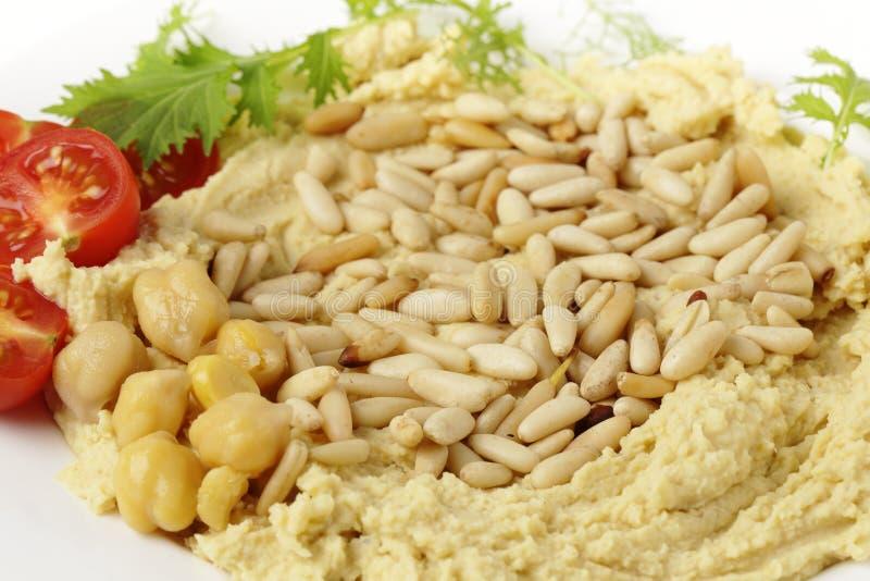 Hummus mit gebratenen Kiefernnüssen lizenzfreie stockbilder