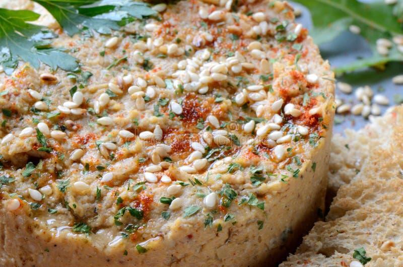 Hummus mit Samen des indischen Sesams und nahem hohem der Petersilie stockbild