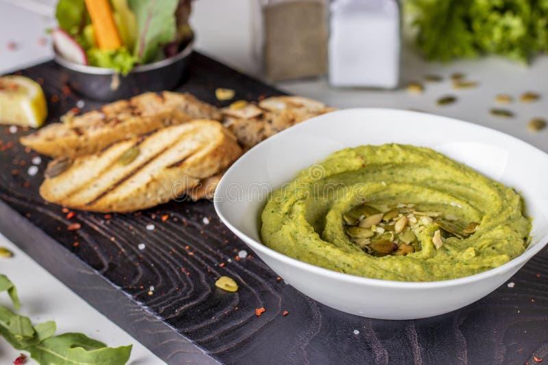 Hummus mit Spinat und Kürbiskernen in einer Schüssel auf einem hölzernen Brett und einem bruschetta, orientalische Küche, horizon lizenzfreie stockfotografie