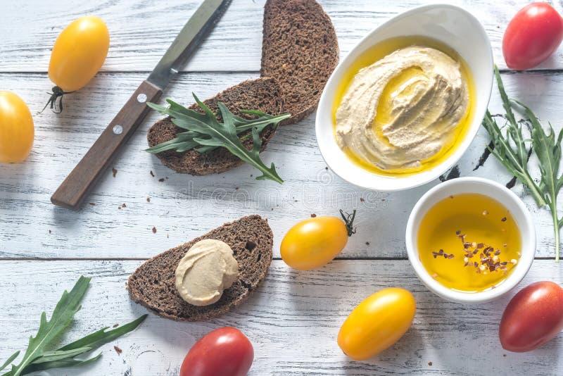 Hummus mit Tomaten und Brot lizenzfreies stockbild