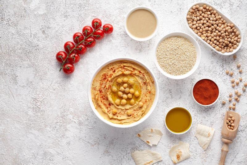 Hummus na configuração lisa com ingridients, alimento natural da bacia da proteína do petisco do vegetariano da dieta saudável fotografia de stock royalty free