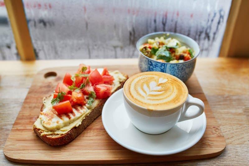 Hummus och tomaten skjuter in, sallad och nytt varmt cappuccinokaffe arkivbild