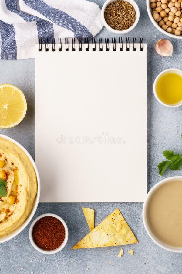 Hummus, open receptenboek en ingrediënten voor het koken stock afbeeldingen