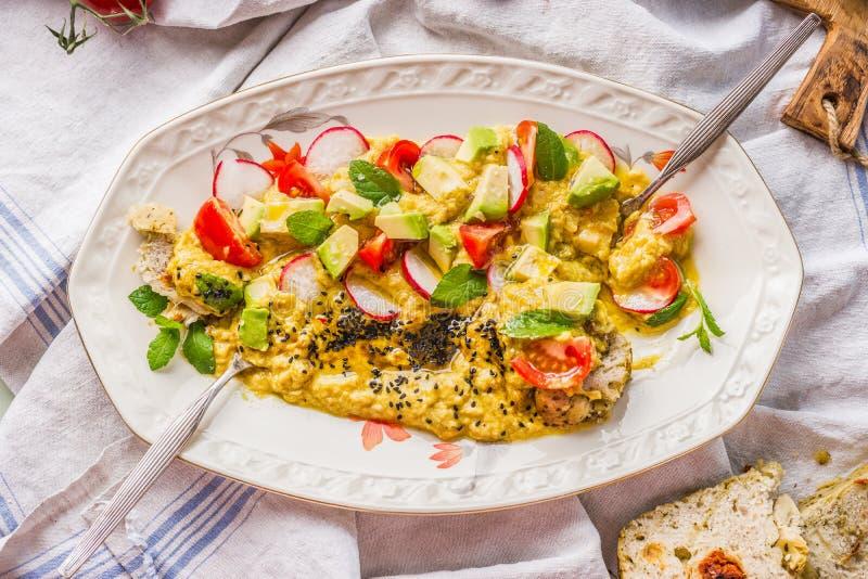 Hummus platta som överträffas med olivolja, avokadot, nya högg av grönsaker och örter på köksbordet med gaffeln och bröd, bästa s royaltyfri fotografi