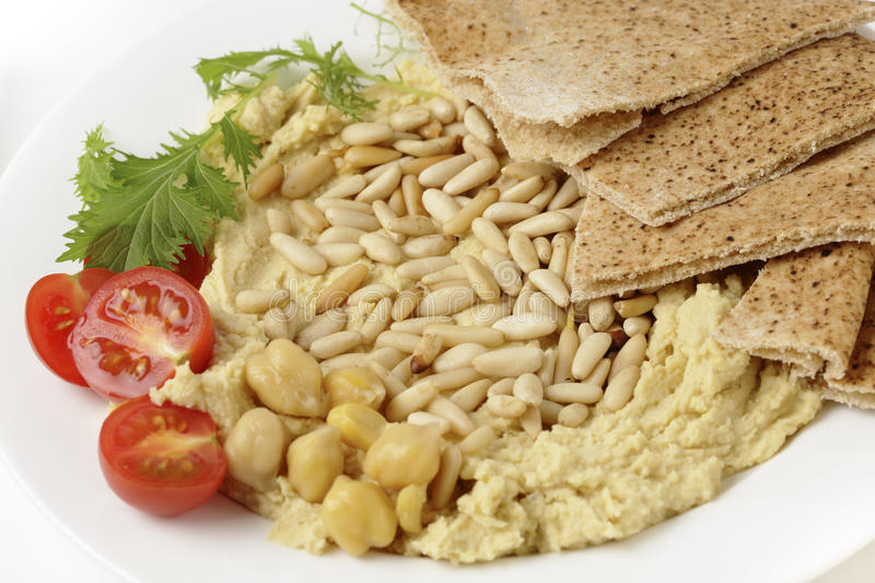 Hummus with roasted pine nuts royalty free stock photos