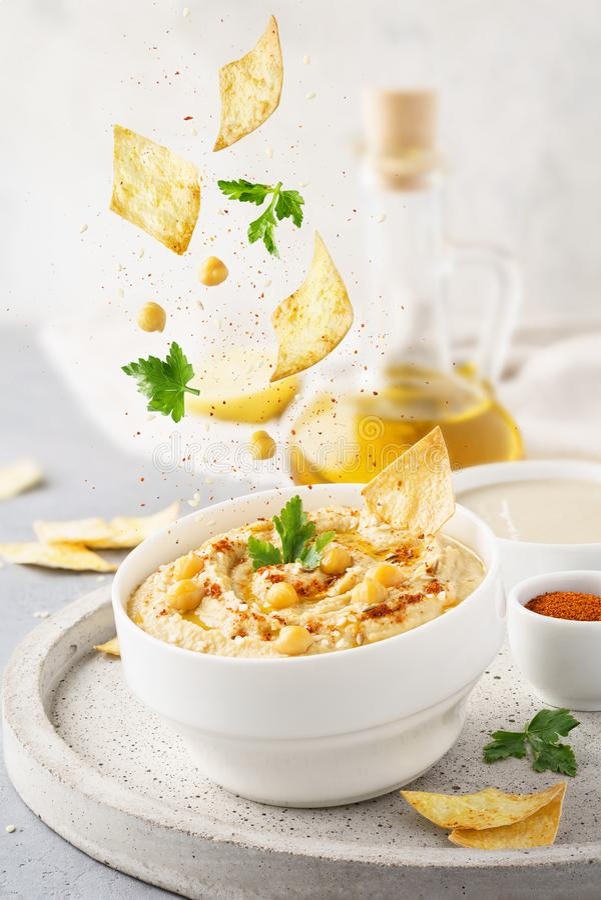 Hummus-Schüssel und fallende Bestandteile Lebensmittellevitation stockbild