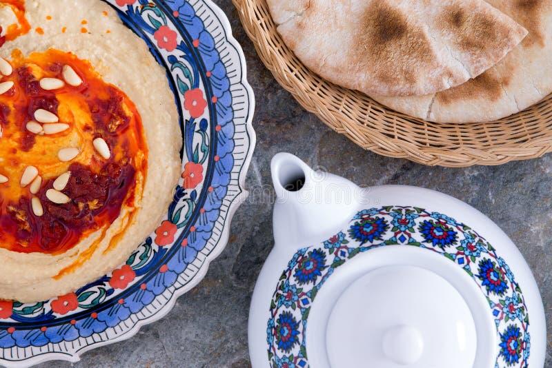 Hummus servito con il pane ed il tè della pita immagine stock