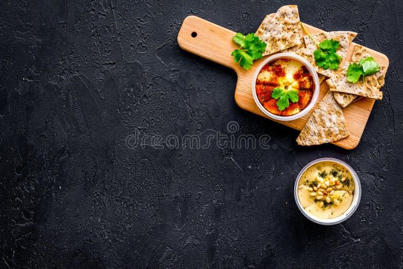 Hummus som är klar att äta Bunke med near stycken för maträtt av knäckebrödet på svart utrymme för kopia för bästa sikt för bakgr royaltyfri bild