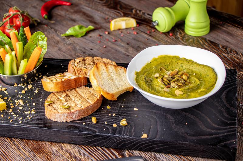 Hummus with spinach, avocado and pumpkin seeds in a bowl on a wooden board and bruschetta, oriental cuisine , horizontal royalty free stock photography