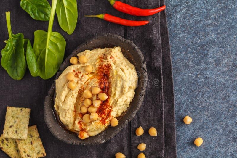 Hummus tradicional hecho en casa en un plato de la arcilla con espinaca y crac fotos de archivo libres de regalías