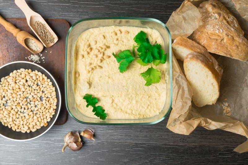 Hummus u houmous, aperitivo hecho de garbanzos triturados con el tahini, limón, ajo, aceite de oliva, perejil, comino en de mader foto de archivo