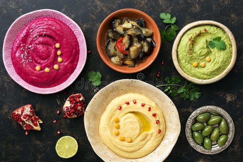 Hummus variopinto in ciotole su un fondo rustico scuro, hummus tradizionale, hummus con basilico, hummus della barbabietola Vista immagini stock libere da diritti