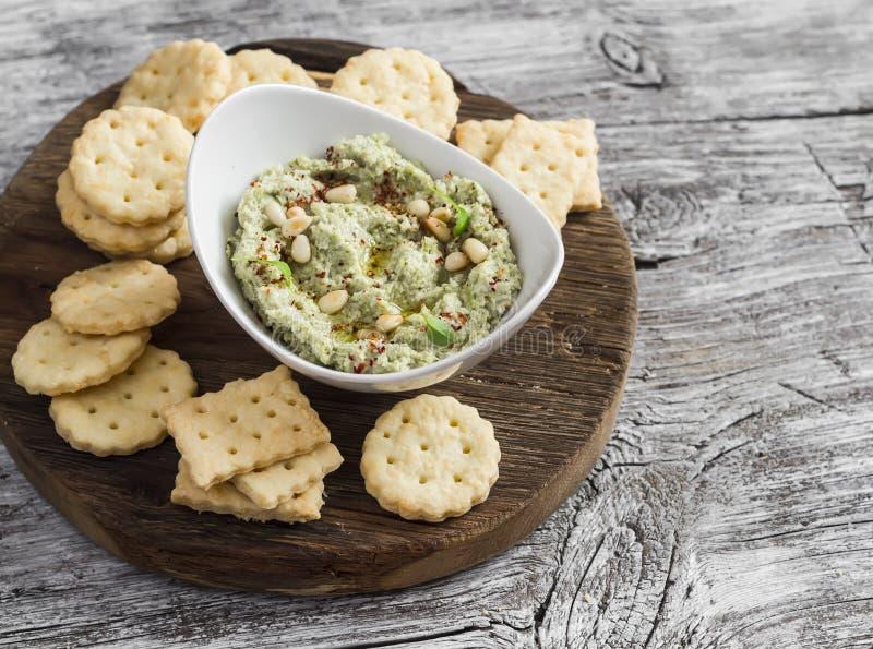 Hummus vegetariano sano de las nueces del bróculi y de pino y galletas hechas en casa del queso en un tablero rústico de madera imágenes de archivo libres de regalías
