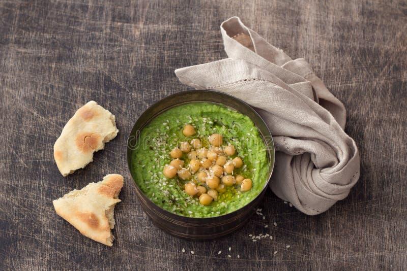 Hummus verde da salsa com grãos-de-bico, sésamo e o pão árabe caseiro em uma tabela de madeira foto de stock royalty free