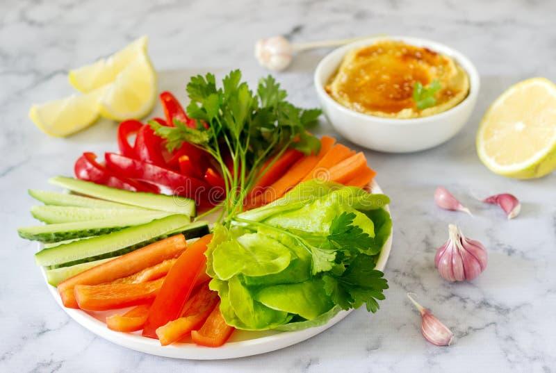 Hummus, verdure differenti e foglie della lattuga con il limone e l'aglio su un fondo leggero Alimento del vegano immagini stock libere da diritti