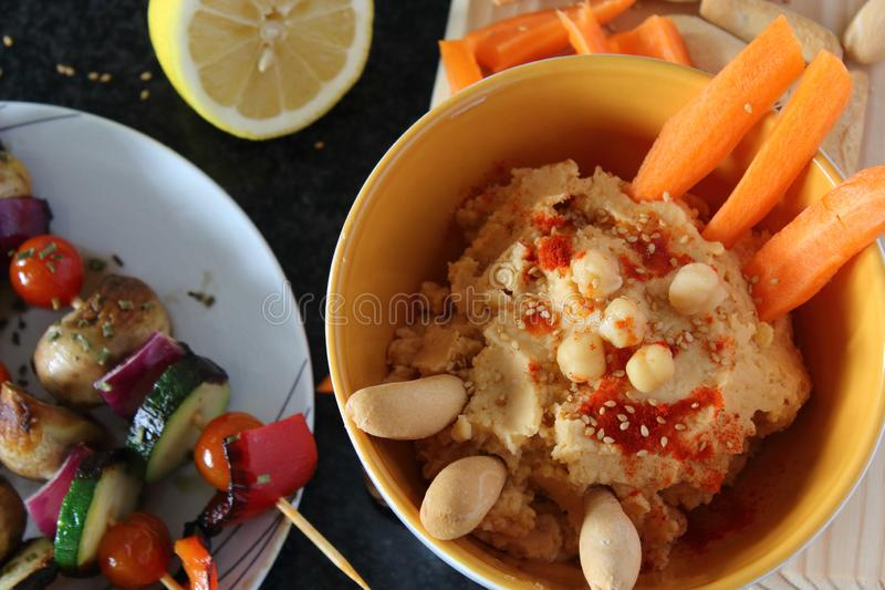 Hummus, verse wortelstokken, brood en gekookte kekers in kom Het concept van het veganistvoedsel, donkere achtergrond stock foto