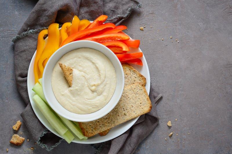 Hummus y verduras en una placa foto de archivo