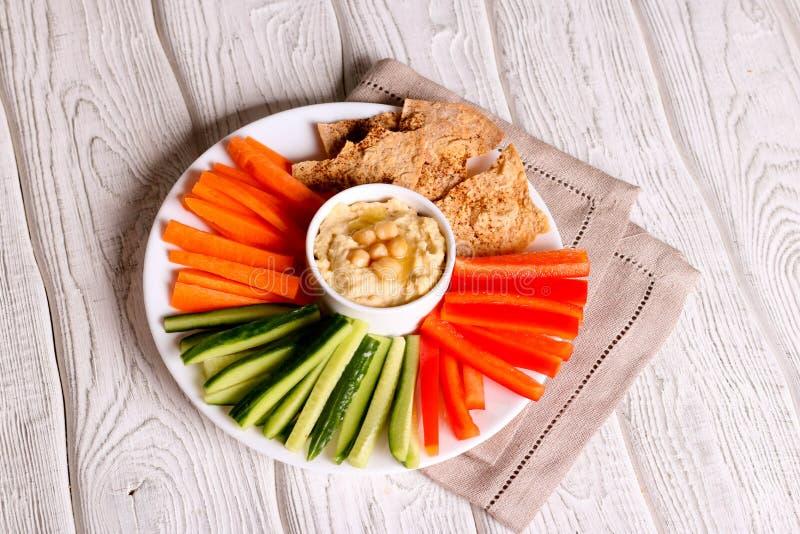 Hummusen för vit böna tjänade som i en bunke med pinnar för den nya grönsaken arkivfoton
