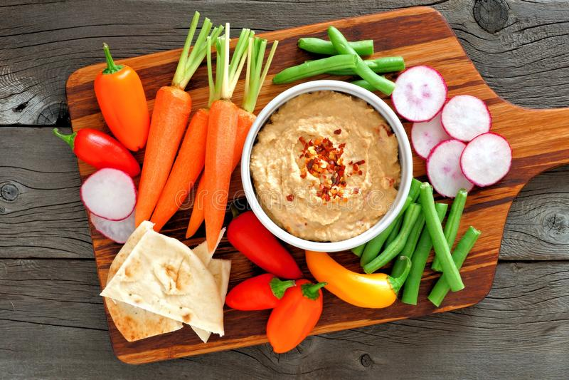 Hummusonderdompeling met een schotel van groenten, over hout stock fotografie