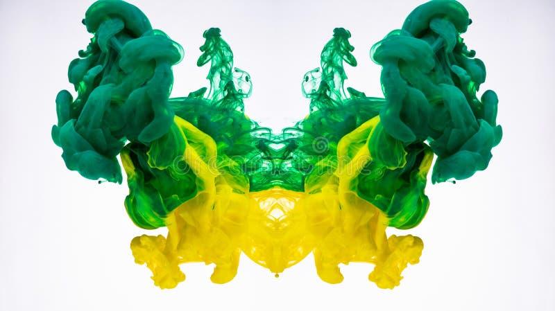 Humo abstracto de la tinta Submarino que remolina del tinte de acrílico Tinta amarilla y verde fotografiada mientras que en el mo fotografía de archivo