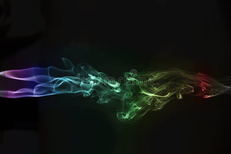 humo abstracto multicolor hermoso en fondo negro fotos de archivo